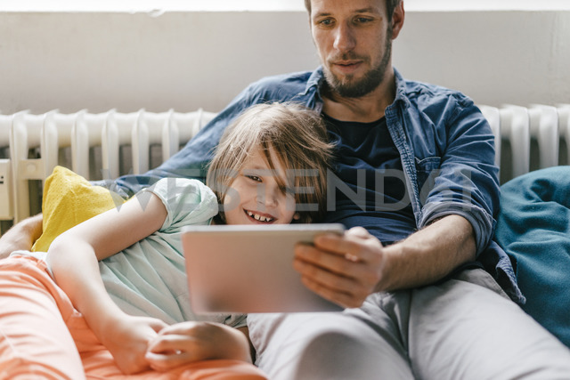 Father and son watching a movie on tablet at home - KNSF03606