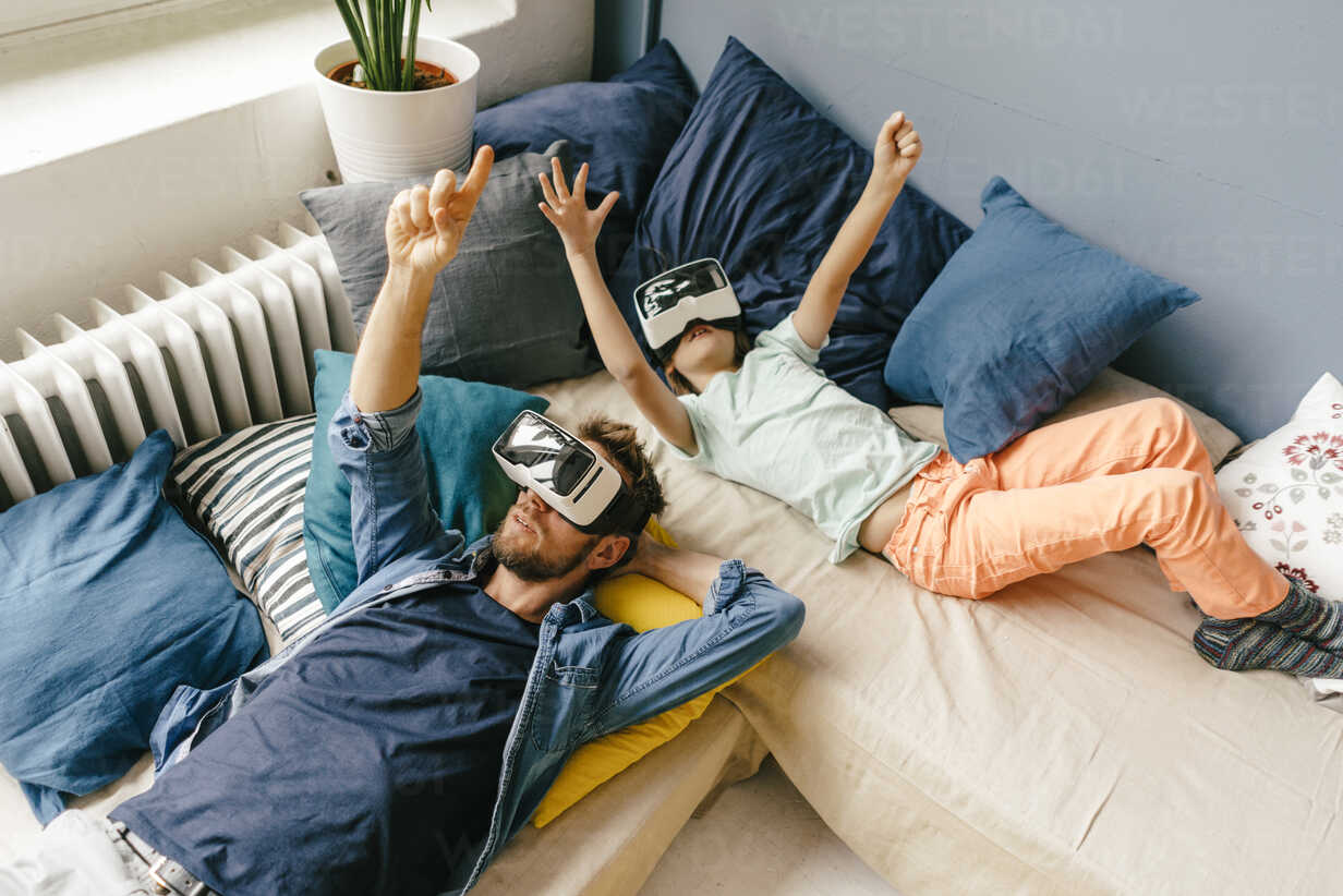 Father and son wearing VR glasses lying down at home - KNSF03609 - Kniel Synnatzschke/Westend61