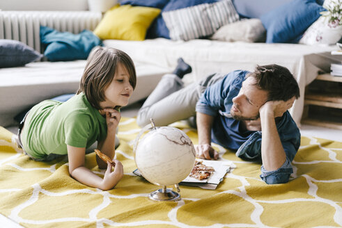 Father and son eating pizza next to globe on the floor at home - KNSF03621