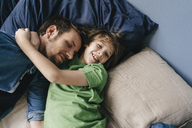 Father and son cuddling at home - KNSF03630