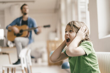 Horrified son covering his ears with father playing guitar at home - KNSF03636