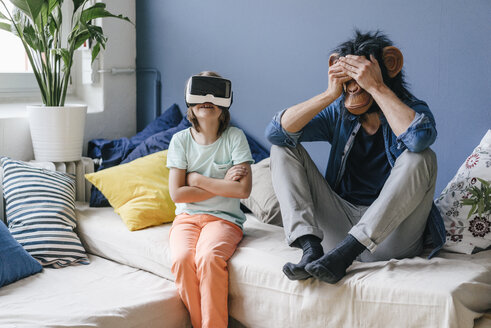 Father wearing monkey mask sitting next to son wearing VR glasses at home - KNSF03648