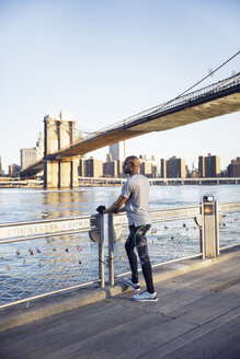 Full length of male athlete standing on promenade with Brooklyn Bridge in background - CAVF27579