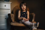 Girl looking away while sitting on armchair at home - CAVF27609