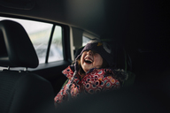 Cheerful girl laughing while sitting in car - CAVF27612