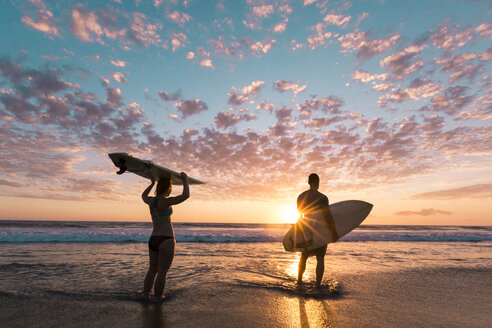Rear view of couple with surfboards standing on shore during sunset - CAVF27693