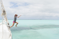 Full length of girl diving in sea from boat against cloudy sky - CAVF27720