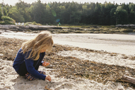Girl picking shells while crouching on sand at beach - CAVF27735