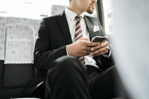 Midsection of businessman holding smart phone while sitting in taxi - CAVF27750