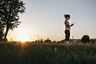 Low angle view of sportswoman using smart phone while standing at grassy field against clear sky during sunset - CAVF27762