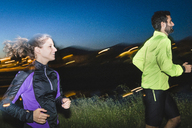 Side view of happy young couple jogging on footpath during night - CAVF27768