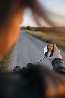 Reflection of female biker seen in side-view mirror - CAVF27774