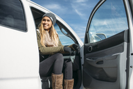 Smiling young woman sitting in car against clear sky during winter - CAVF27909