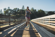 Sportswoman running at wooden bridge on sunny day - CAVF27951