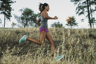 Low angle view of sportswoman running on grassy field - CAVF27957