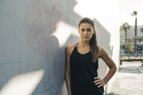 Portrait of confident female athlete leaning on wall outdoors - CAVF28047