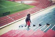 High angle view of sportswoman running on steps at stadium - CAVF28176