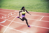 High angle view of determined female athlete running on tracks - CAVF28185