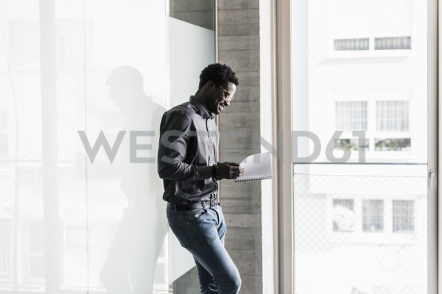 Smiling businessman standing at the window looking at notepad - UUF13089