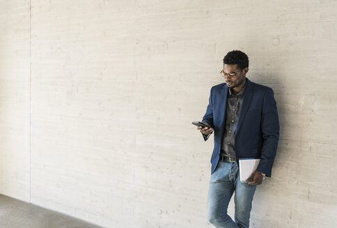 Businessman standing at concrete wall looking at cell phone - UUF13092