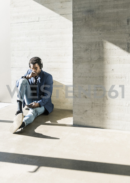 Businessman sitting on the floor in sunshine  wearing headphones looking at cell phone - UUF13095