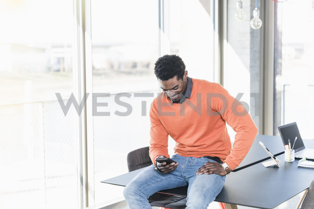 Smiling casual businessman looking on cell phone in office - UUF13107
