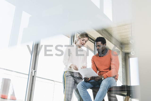 Casual businesswoman and businessman discussing papers in office - UUF13110