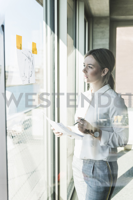Young businesswoman looking at paper at the window - UUF13113