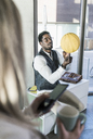 Businessman balancing basketball in office - UUF13119