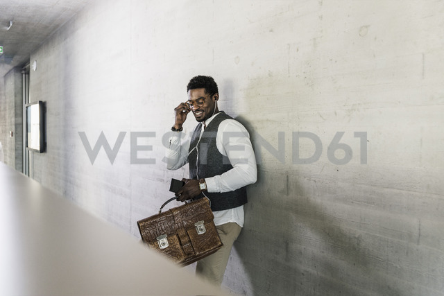 Businessman standing at concrete wall with earphones, cell phone and briefcase - UUF13122