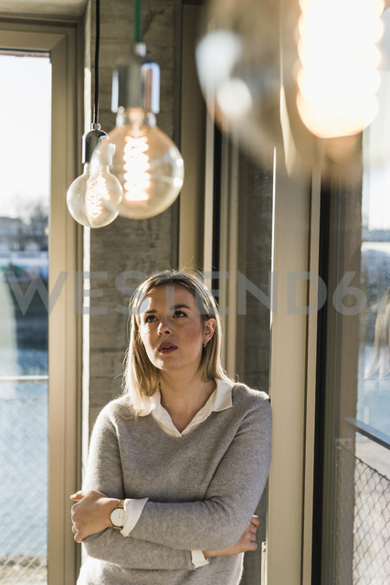 Young businesswoman in office looking at light bulbs - UUF13125