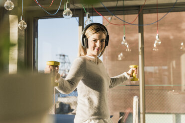 Portrait of smiling young businesswoman exercising with dumbbells in office - UUF13134