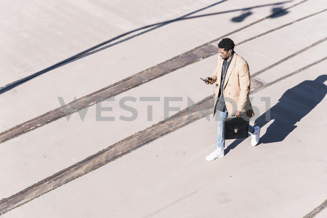 Businessman walking outdoors with briefcase, cell phone and earphones - UUF13137