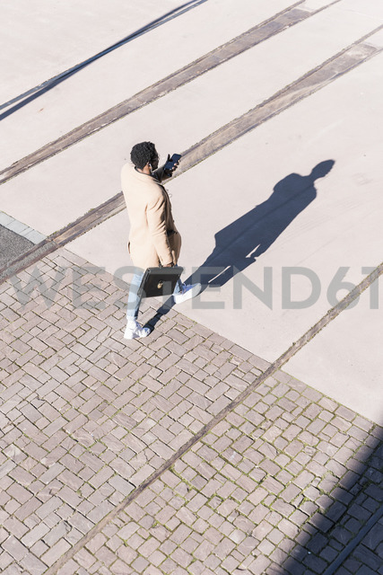 Businessman walking outdoors with briefcase, cell phone and earphones - UUF13140