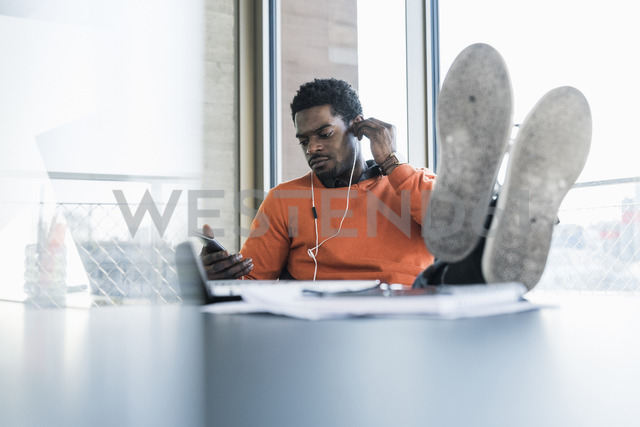 Casual businessman with earphones sitting at desk looking at cell phone - UUF13149