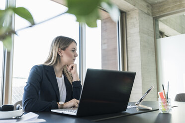 Young businesswoman working with laptop at desk in office - UUF13155