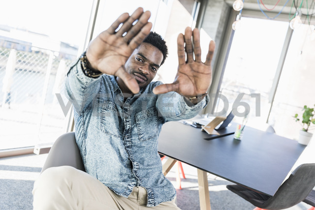 Portrait of smiling casual businessman in office making a finger frame - UUF13158