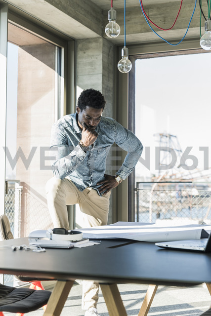 Casual businessman working on plan at table in office - UUF13161