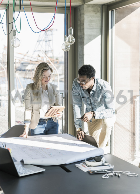 Two colleagues working on plan at table in office - UUF13164