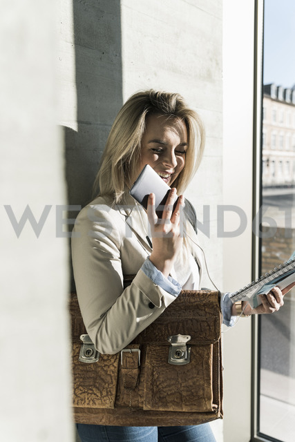 Happy young businesswoman using smartphone at the window - UUF13170