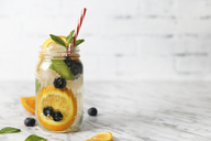Glass of infused water with orange, blueberries and mint on ice - RTBF01102