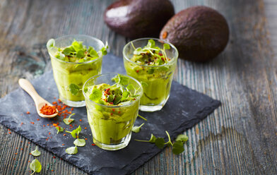 Glasses of avocado cream with chili flakes, cress and parsley - KSWF01837