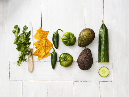 Avocados, green tomatoes, Jalapeno peppers, cucumber, parsley, kitchen knife and tortilla chips on white wood - KSWF01843