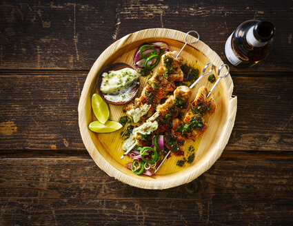 Grilled chicken skewers and garlic mayonnaise on plate, beer bottle - KSWF01870