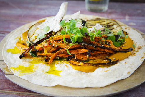 Pulled Chicken Wrap, carrot, grilled aubergine, curry hummus, herbs on chopping board - KSWF01876