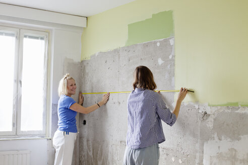 Young women measuring wall for renovation - FOLF00033