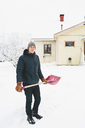 Man standing with pink snow shovel in front of house - FOLF00111