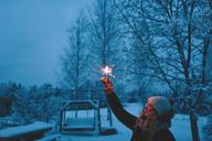 Smiling woman holding sparkler in backyard at dusk - FOLF00117