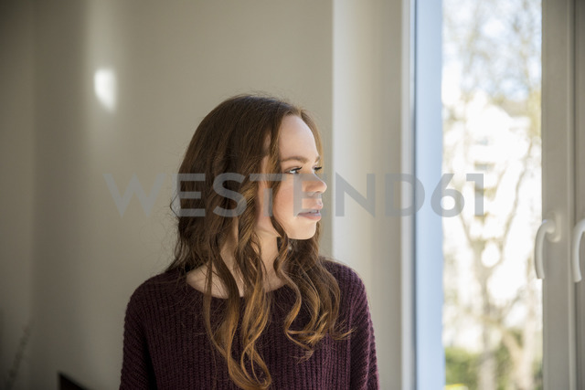 Teenage girl looking out of window, daydreaming - FMKF04986