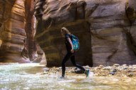 Portrait of female backpacker walking in river by mountains - CAVF28386
